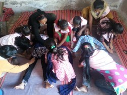 Young girls outline each other with chalk at the beginning of a body mapping activity, which will led into a discussion about gender.