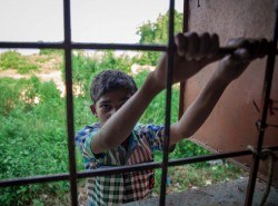 A child who's not enrolled in AIF's LAMP courses in Ganiary looks on from outside our Learning Resource Center