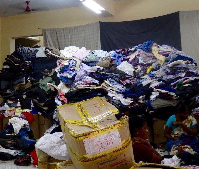 Sorting piles at Goonj's office in Chennai.  A group of women sifted through each piece labeling it category A, B, or C.