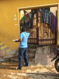 One of SAFA staff handing out a pamphlet to a woman peeking out from her home