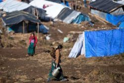 In January 2016, a woman walks through the earthquake camp in Gupsi, Pakha, Laprak, in Gorkha District. ©