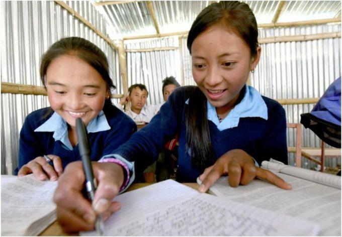 Two girls study inside a UNICEF-supported temporary learning center in Dhunche, one of the worst earthquake-affected areas. © UNICEF