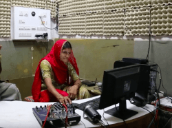 A woman editing a radio program at Barefoot College community radio station