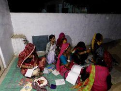 Picture 1: - The women at the night school being helped by their facilitators- Sunita (in a purple suit) and Nitu (in a red t-shirt with her back towards the camera)