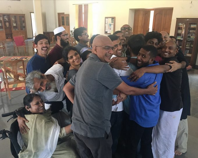 Several participants gathered in a large group hug, turning to face the camera and smiling.