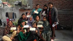 The image is of a group of 11 women smiling and holding their cheques.