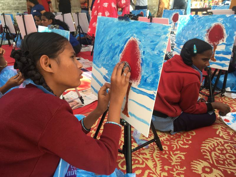 A girl applies red paint to a painting, in front of a blue background. She dabs red paint using her right hand and feels the surface of the painting with her left hand.