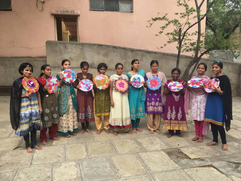 All 11 girls standing in a courtyard, holding their finished collages in front of their chests and smiling for the camera.