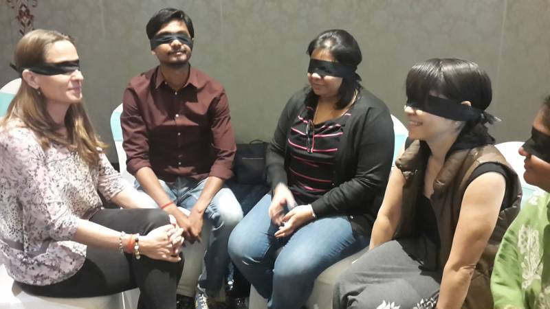 Four people sit in a semicircle, their eyes covered by black blindfolds. They seem alert and listening.