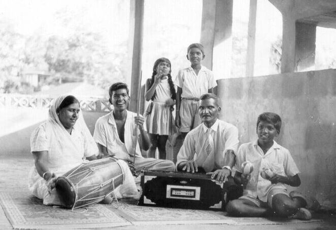 A woman playing an Indian drum and a man playing the harmonium are surrounded by their four children.