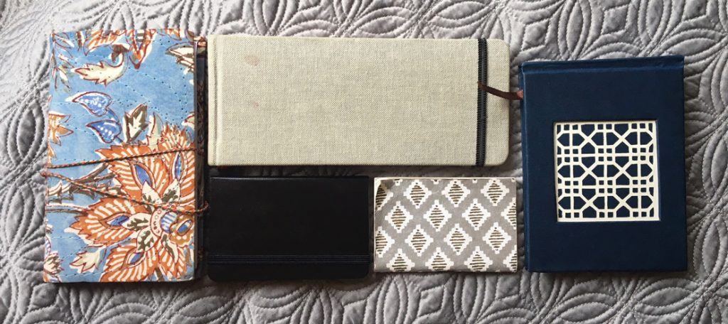 Five notebooks of various sizes and colors arranged into a rectangle.