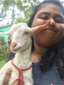 Close-up photo of Nithya holding a white baby goat, one of the goat's ears brushing Nithya's nose.