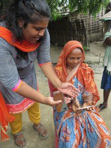 Photo of Nithya handing a tablet to an Indian woman sitting on a chair outside, explaining something.