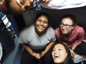 Photo of Nithya and three female friends on an overnight train, smiling into the camera.