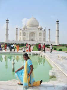 Photo of Nithya as a young girl wearing a kurta and posing in front of the Taj Mahal.