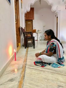 Photo of a female colleague of Nithya's, sitting cross-legged in front of a lit red candle, appearing to reflect or pray.