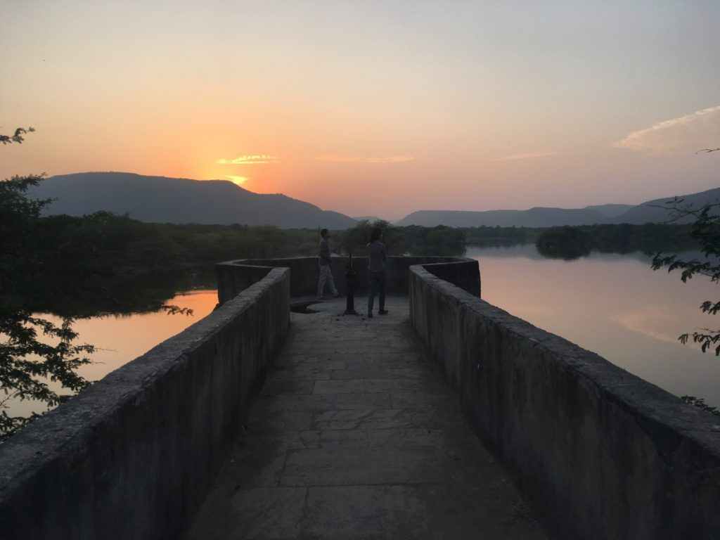 Walkway out to a viewing point over a lake with mountains in the background at sunset