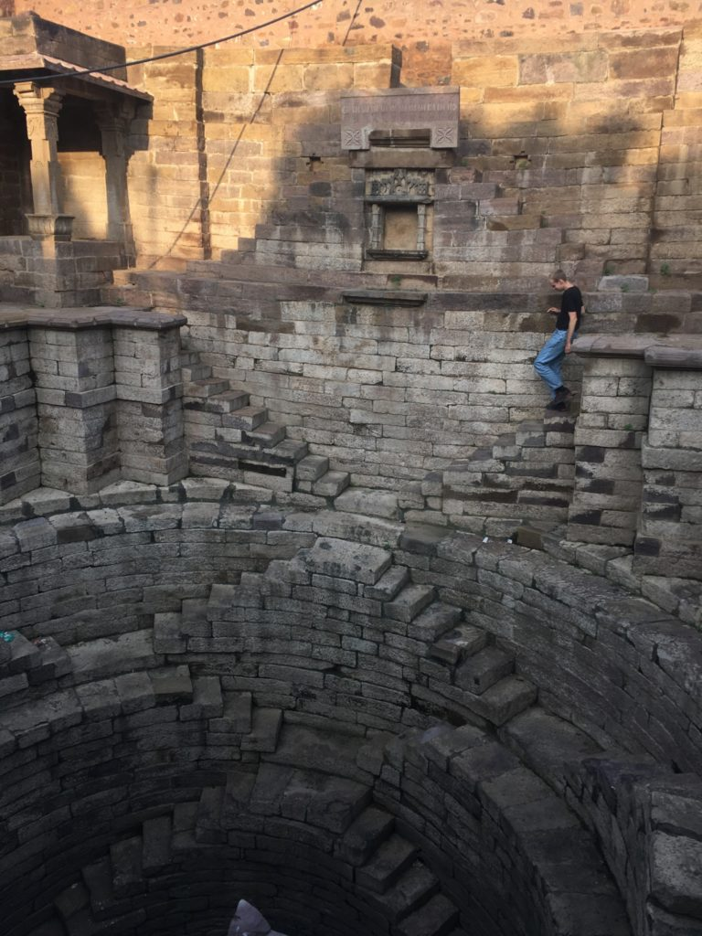 A person walking down stairs to a round step well