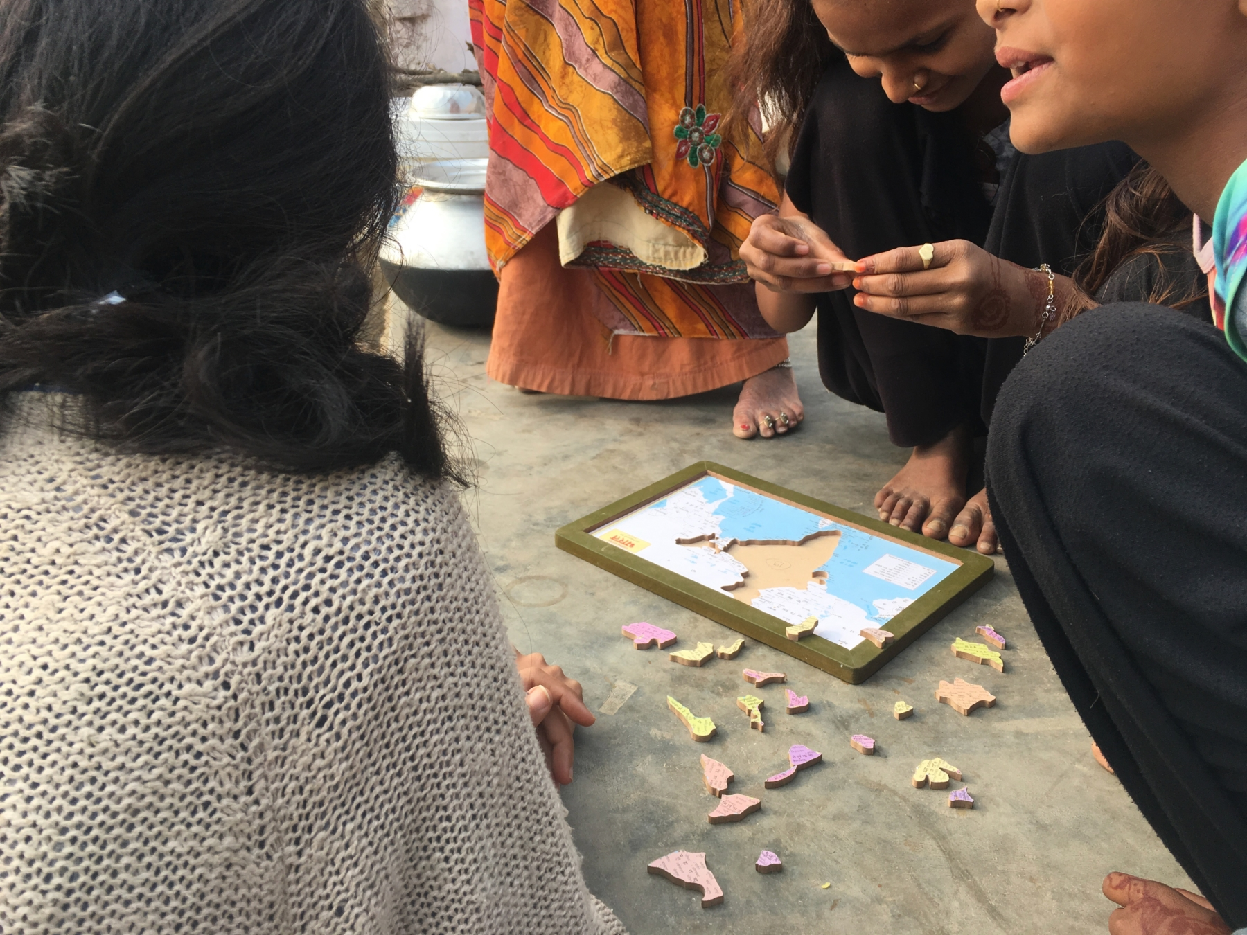 People gathered around an Indian geography puzzle