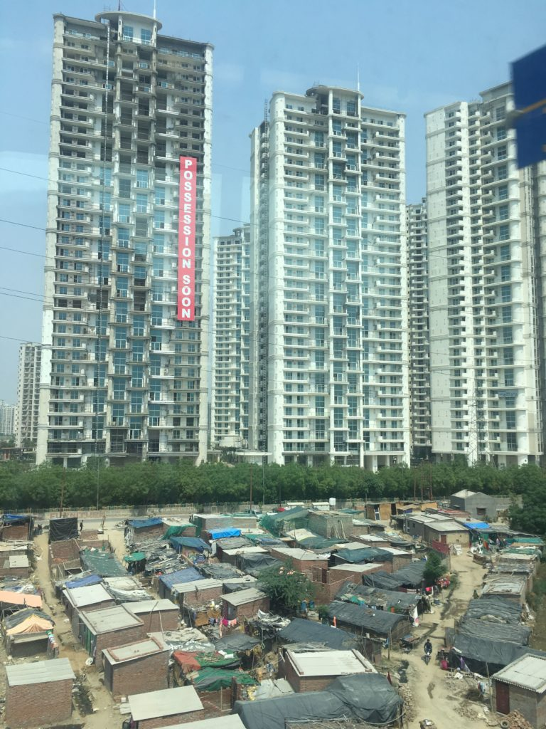 """New high rises with a sign that says """"POSSESSION SOON"""" above an informal settlement"""