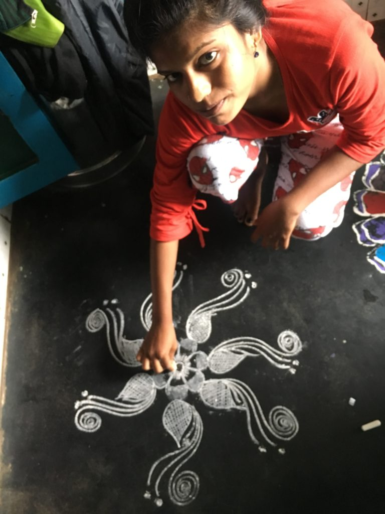 Yasoda a adolescent girl of Odisha drawing jhuti in the entrance of her house