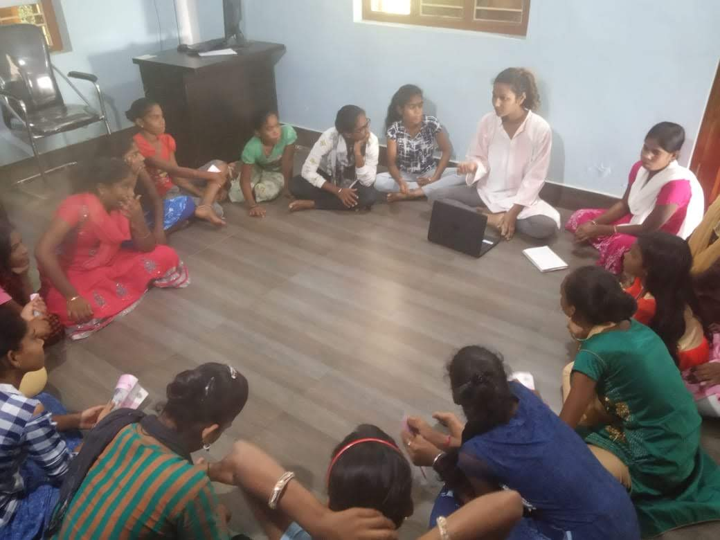 A group of adolescent girls seating in a circle. its a office location in which the group is seating on floor.