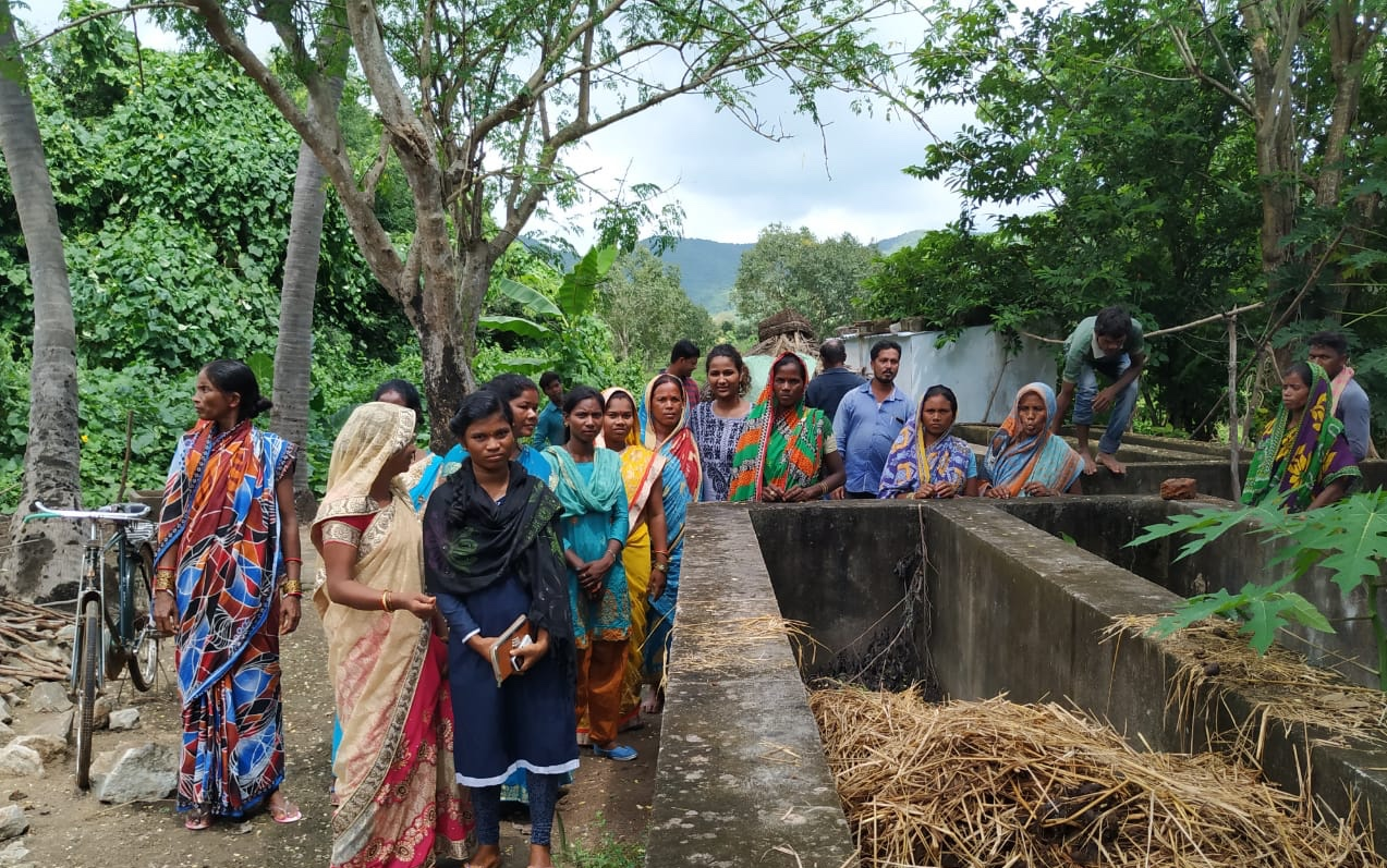 A group of women farmers standing beside the vermicompost and trying to learn the process.