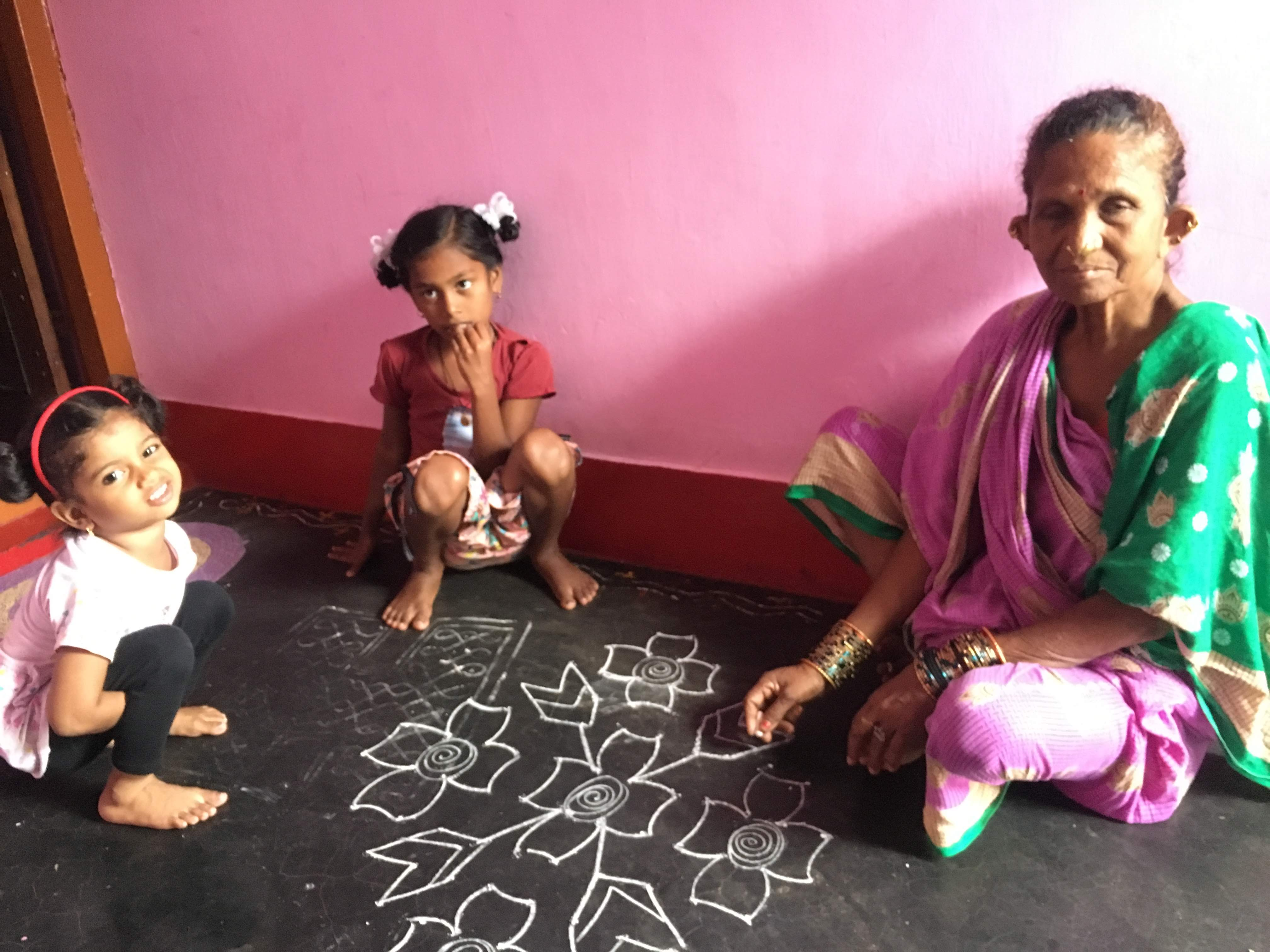An elderly women with two of her grand daughters seating in a cemented floor and making Muggulu
