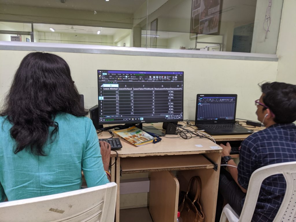 Two visually impaired people sitting in front of computers.