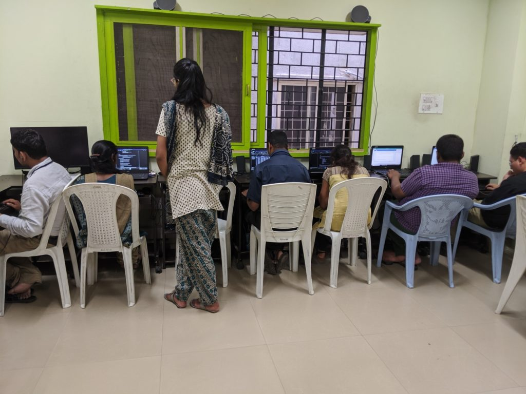 A row of students at computers, while a teacher looks on