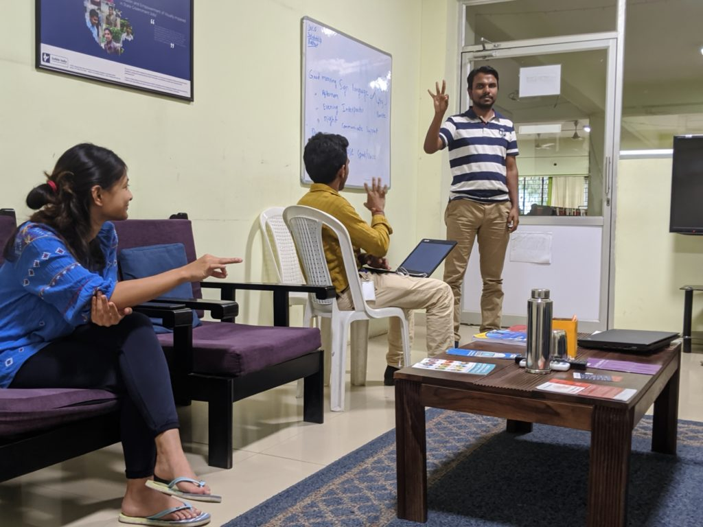 Three people making signs in sign language