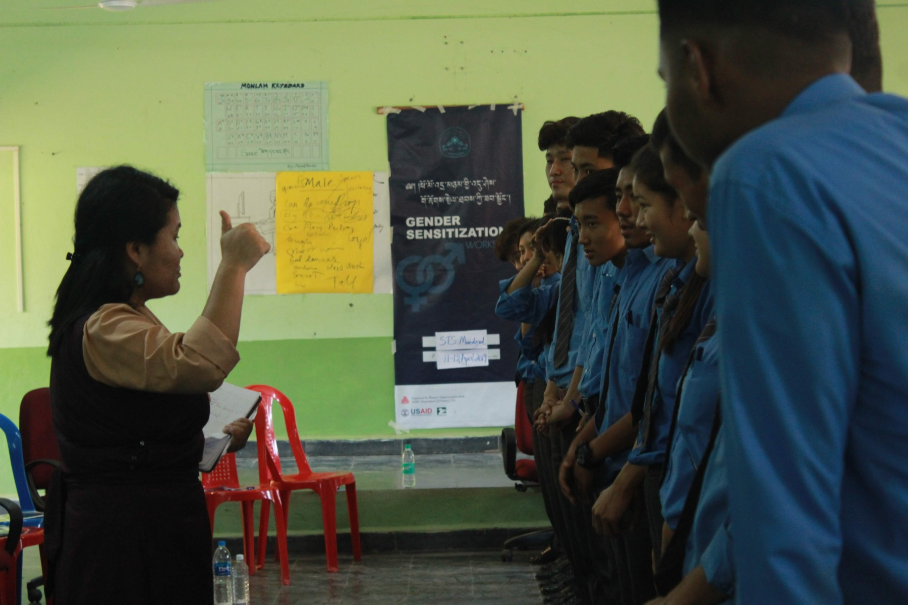 Gender Sensitization Workshop in progress. A woman teaching a class of teenage boys. The poster in the background reads 'Gender Sensitization'.