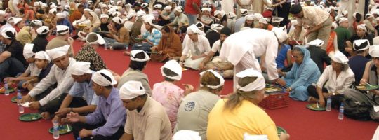 People serving and eating food at a langar in a gurudwara