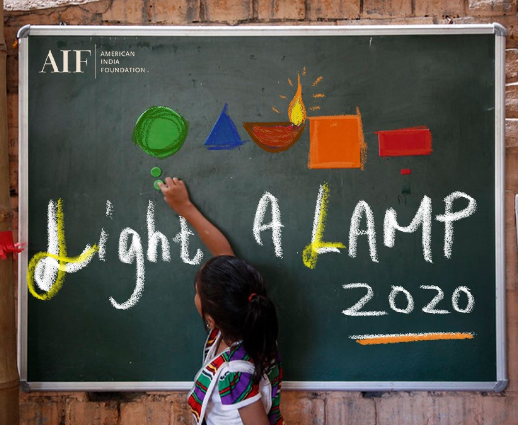 "School girl drawing ""Light a LAMP 2020"" on a board"