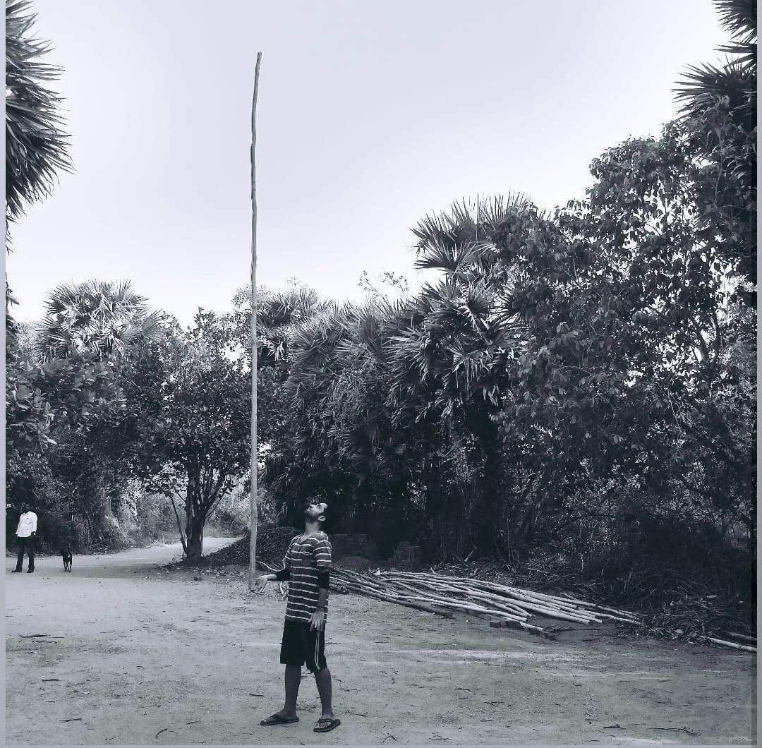 Aman carefully balancing a 12-foot-long bamboo stick on his finger.