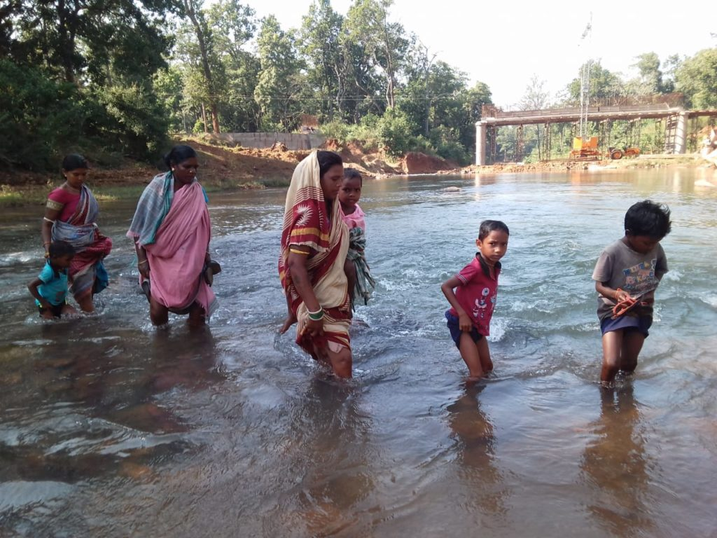 Villagers from M Rampur crossing Rahul river on foot with knee-level water to attend the Regular Immunization session