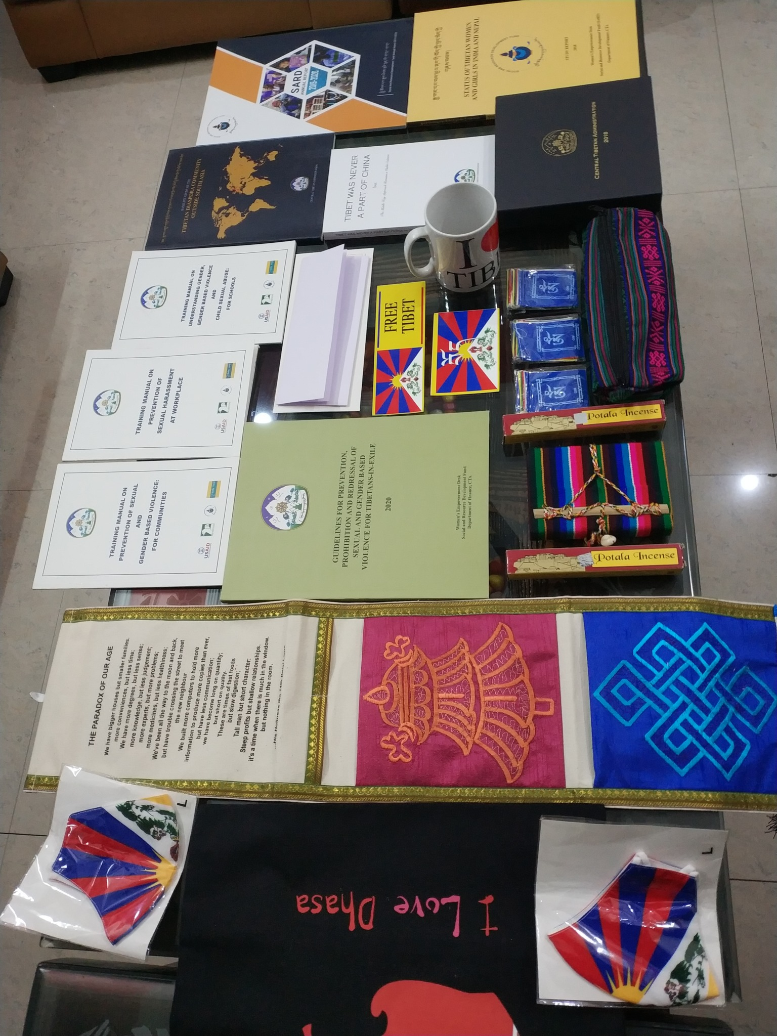 Brochures, books and other educational material, flyers, incense, stickers, a porcelain cup with CTA logo, Tibetan prayer flags, a pen pouch and notebook diary in traditional Tibetan print, personal protective masks, and banners of the CTA.