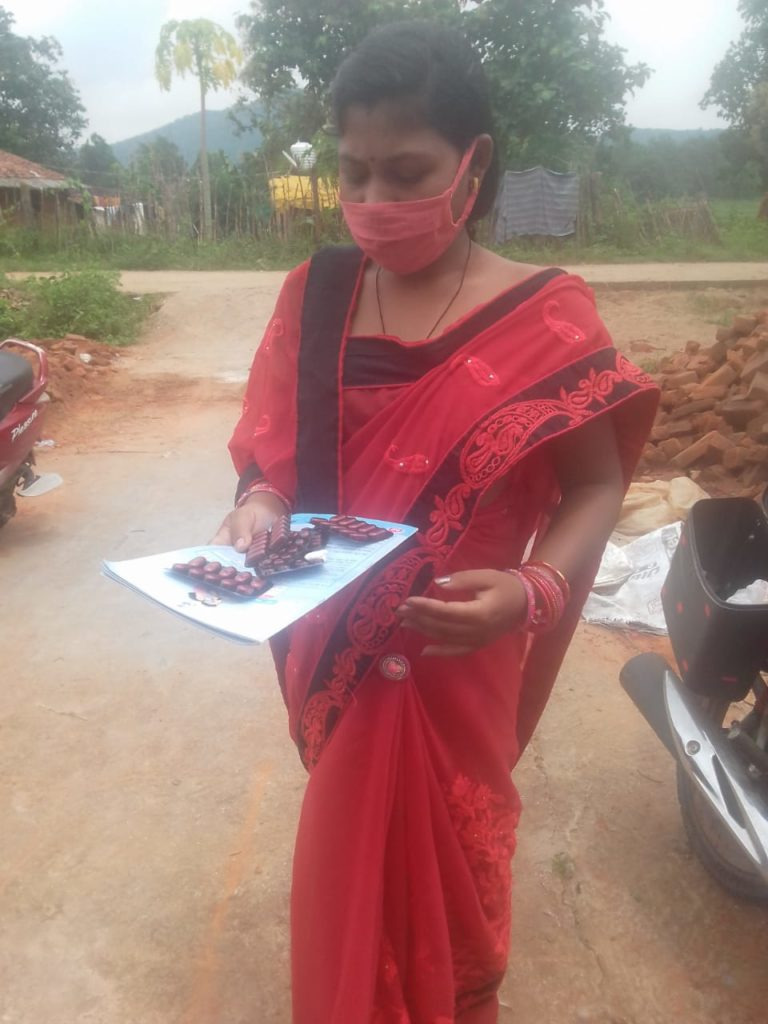 A pregnant woman is holding Iron-Folic Acid tablets after a IFA Distribution Camp in Khaliamunda village