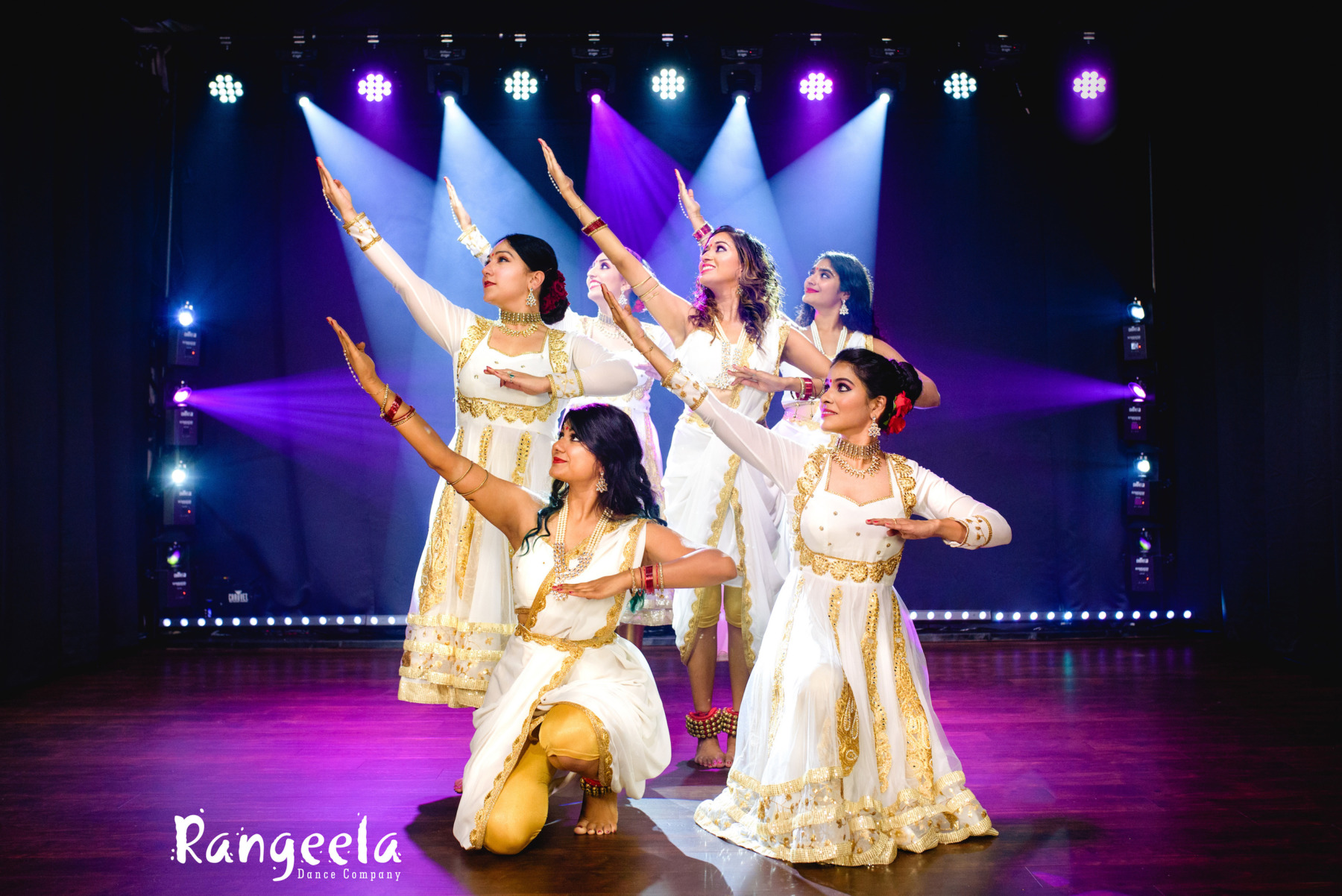 Priyanka performing with 5 other dancers from Rangeela Dance Company, dressed in modern anarkali suits in white and gold.