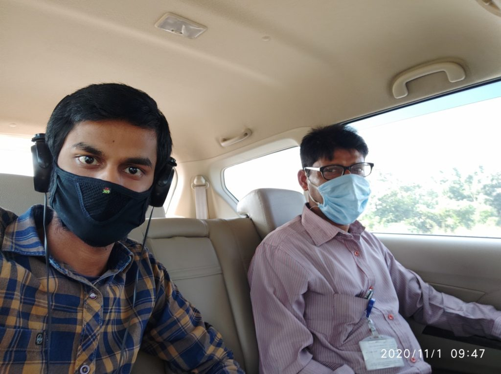 Shashi and his father in a car, with masks on.