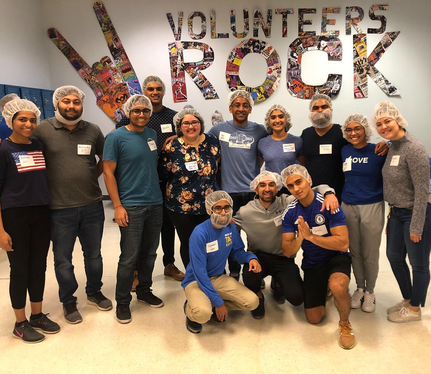 """Sayuj with twelve Seattle young professionals with hair nets and masks posing in front of a """"Volunteers Rock"""" mosaic."""