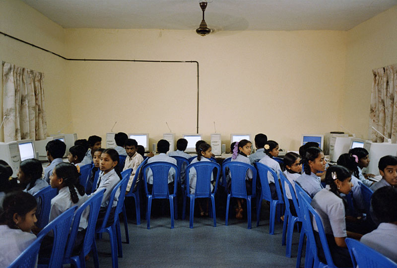 Children in school uniforms sitting on plastic chairs, working on computers lined up on desks.