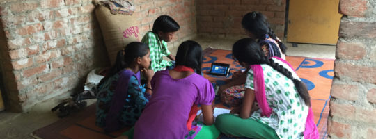 Children watch videos sitting crowded around a small tablet.