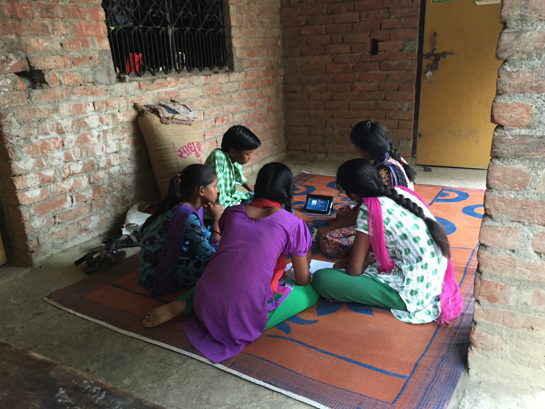 5 children sitting around a small tablet computer placed on the carpet, watching a video.