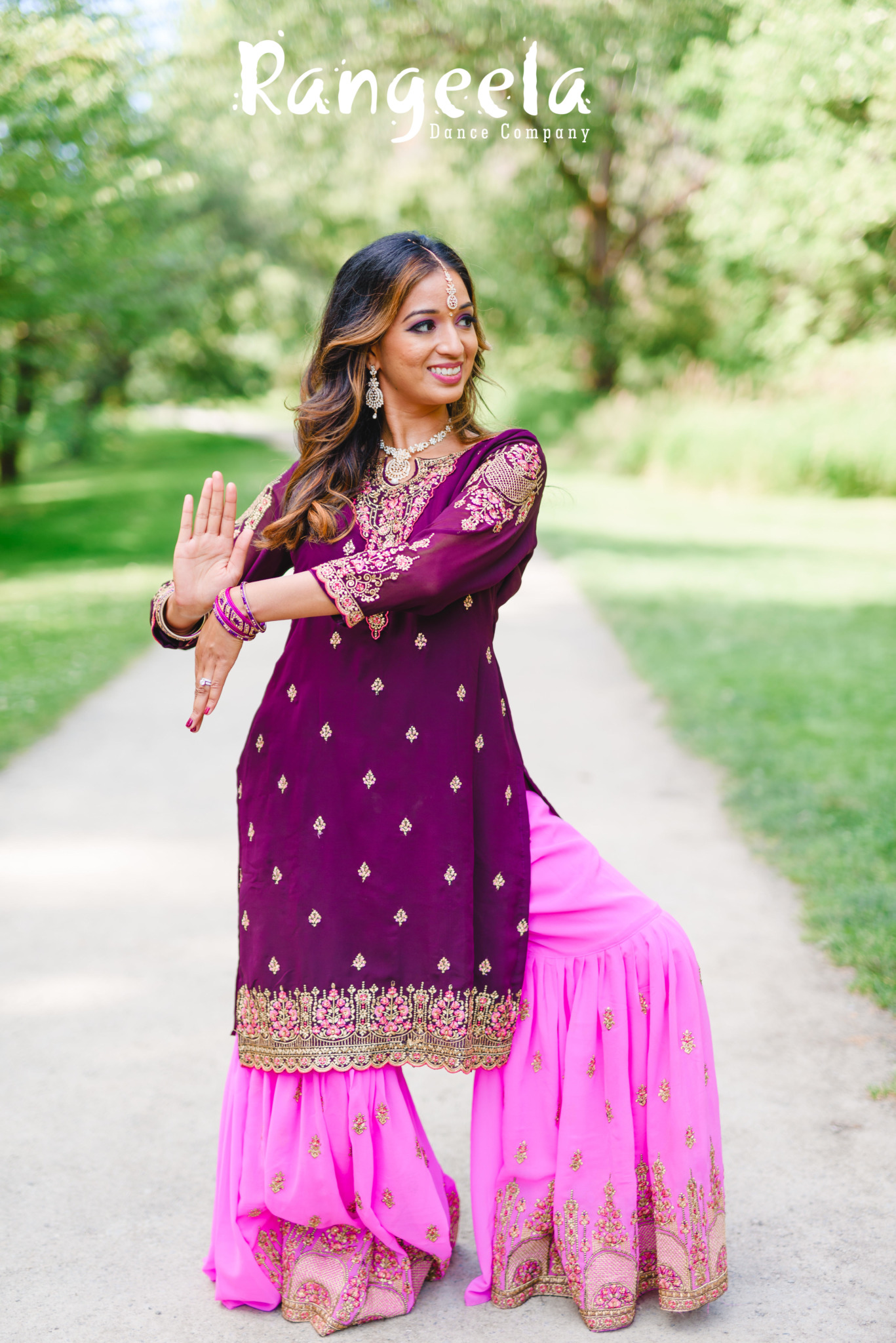 Priyanka posing in a traditional sharara salwar kameez in purple and pink, with gold decorations.
