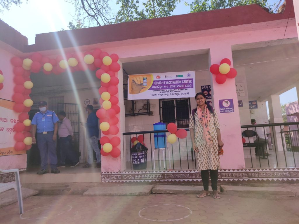 Anushri is standing below the banner about the Largest Vaccination Drive, she is standing with nobody near her.