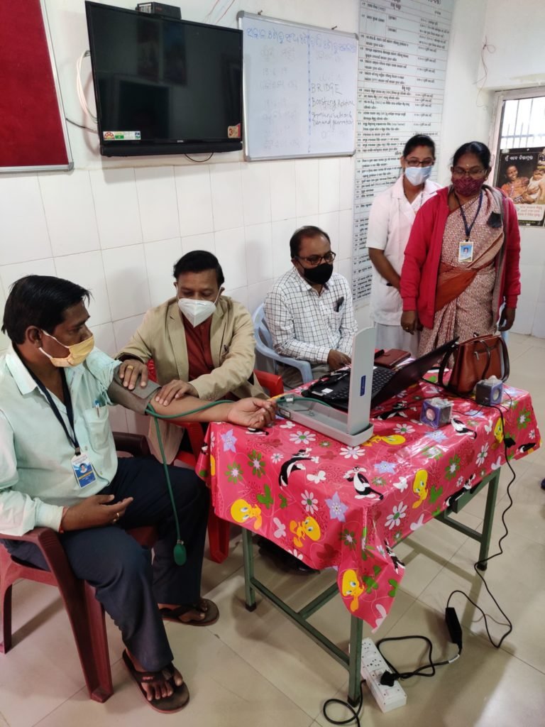 Inside this room, two men are sitting around a table, one is checking the blood pressure of another man who got vaccinated and is now sitting on the side of the table. One nurse and a representative from National Health Mission are overlooking this procedure
