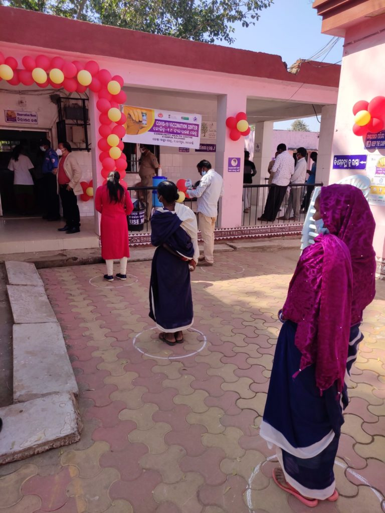 Three women are standing within circles made on floor to maintain COVID-19 appropriate behaviour. The entrance to the rooms is decorated with red and yellow balloons to mark the largest vaccination drive.
