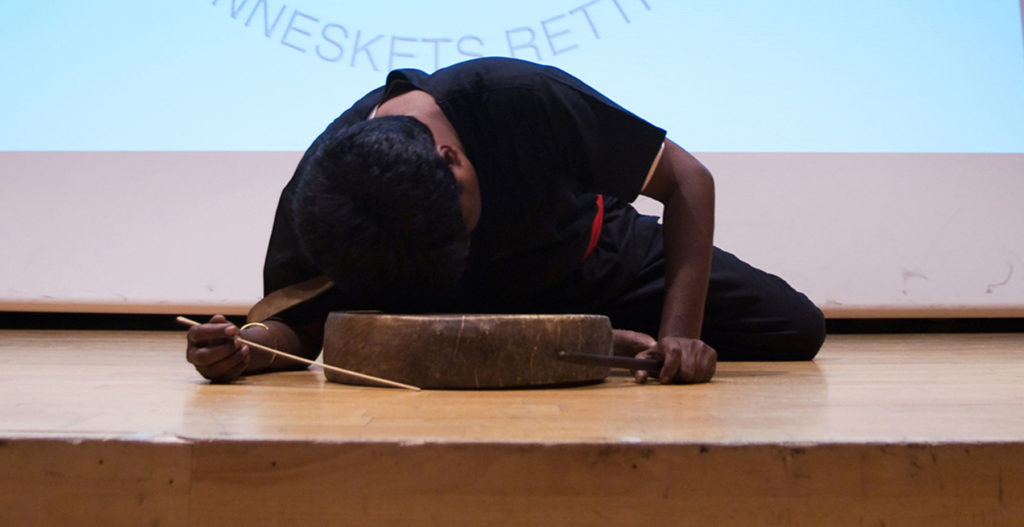 Suresh performing with the dappu drum on stage.