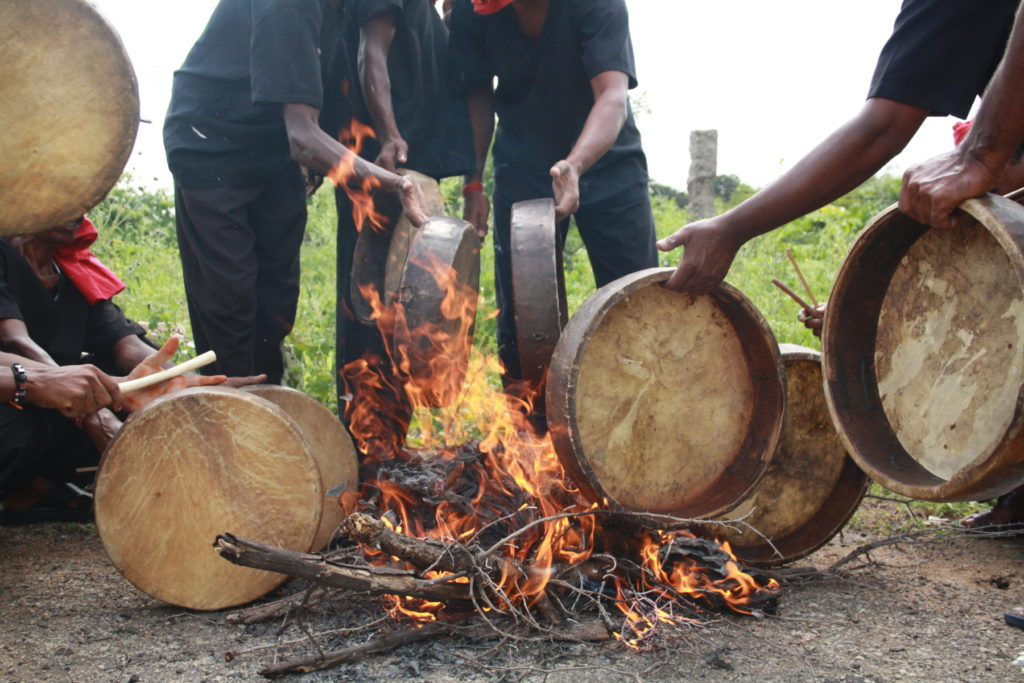Dappu drums being tuned by heating over a fire.